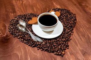 tasse à café blanche, pain d'épice en forme de coeur et deux cuillères sur un coeur photo