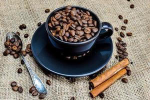 Tasse à café noire pleine de grains de café bio et de bâtons de cannelle sur un chiffon en lin photo