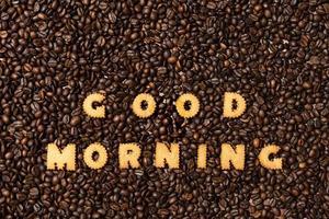 Les mots bonjour fabriqués à partir de lettres de biscuit sur un fond de grain de café foncé