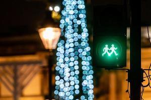 sémaphore pour piétons avec feu vert et lumières d'arbre de Noël défocalisés