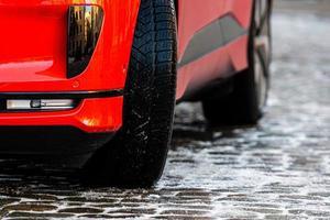 gros plan, de, a, voiture rouge, à, pneus hiver, sur, a, trottoir verglacé photo