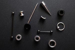 Articles pour un piercing en métal sur fond gris foncé photo