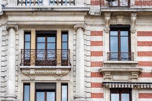 Façade d'un bâtiment historique en brique avec balcons métalliques photo