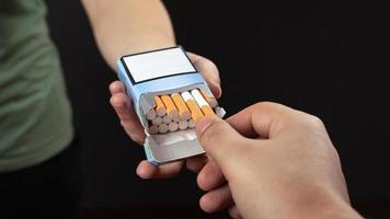 personne remettant des cigarettes à une autre personne photo