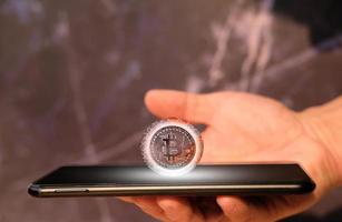 Pièce de monnaie de crypto-monnaie bitcoin et pièce en euro sur smartphone, concept photo