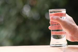 Eau potable minérale sur table en bois et eau en verre photo