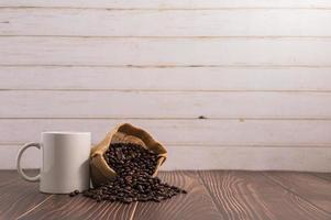 Une tasse de café avec un sac de grains de café sur une table en bois photo
