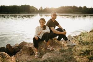 un jeune père avec une barbe et des lunettes de soleil pose avec sa jolie fille sur la côte photo