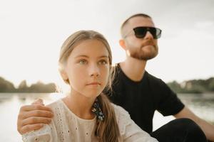 un portrait proche d'une jeune fille qui pose avec son père avec une barbe qui la serre dans ses bras photo