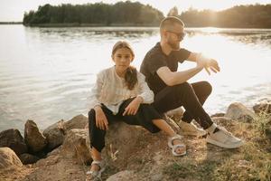 un jeune père avec une barbe et des lunettes de soleil est assis sur des pierres avec sa fille et vérifie la smartwatch le soir