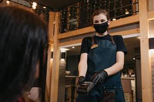 une serveuse porte un masque médical et des gants médicaux jetables remettant un terminal de paiement sans fil à une cliente photo
