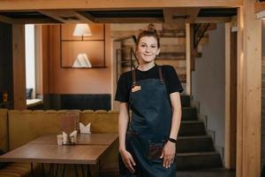 une jeune serveuse souriante pose dans un restaurant photo