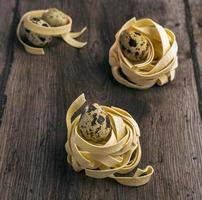 Oeufs de caille dans les nids de pâtes sur un fond de bois photo