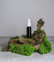 Bouteille en verre de sérum avec une pipette sur mousse verte, concept cosmétique spa bio naturel photo