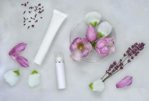 Phytothérapie avec fleurs de magnolia et lavande, boîtes de Pétri, tubes cosmétiques et fond de soins naturels photo