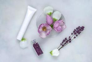 Phytothérapie avec des fleurs de magnolia, des boîtes de Pétri et des tubes de cosmétiques, fond de soins naturels photo