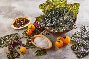 Algues nori croustillantes aux tomates cerises et épices dans un bol en bois sur béton gris