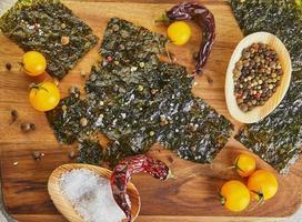 Algues nori croustillantes aux tomates cerises et épices sur une planche de bois