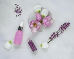 Fond de soins cosmétiques de boîtes de Pétri et de tubes cosmétiques de phytothérapie avec des feuilles vertes et des pétales photo
