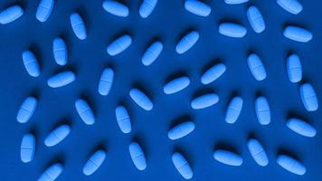 Capsules de comprimés sur fond bleu, plat simple monochrome poser avec concept médical de texture pastel photo