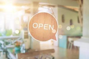 un panneau commercial qui dit ouvert sur une porte suspendue à l'entrée d'un café ou d'un restaurant