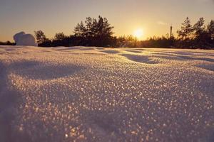 neige au premier plan sur une soirée d'hiver glaciale au coucher du soleil photo