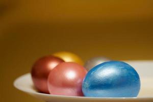 Oeufs de Pâques de couleur nacrée dans une boîte à œufs sur fond doré photo