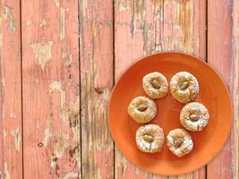 Cookies sur une plaque orange sur un fond de table en bois photo