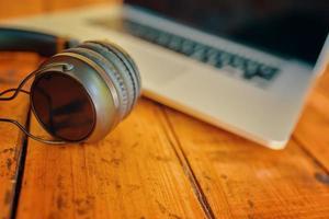 ordinateur portable et casque sans fil sur table en bois photo