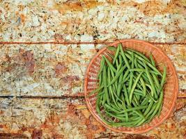 Haricots verts sur une plaque en osier sur un fond de table en bois photo