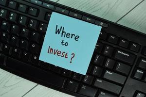 où investir écrit sur le bloc-notes isolé sur table en bois photo