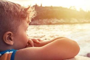 Gros plan du garçon voyageant en bateau au coucher du soleil photo