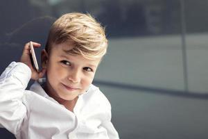 mignon petit garçon parlant au téléphone mobile photo