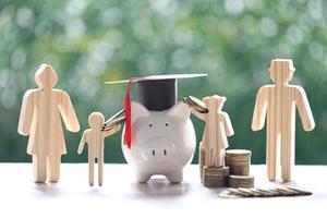 Graduation hat sur tirelire avec famille modèle et pile de pièces sur fond vert naturel photo