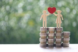 Découpe de couple et pile de pièces d'argent sur fond vert naturel photo