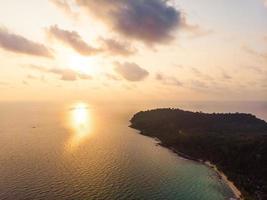 Vue aérienne de la belle plage et de la mer avec cocotier au moment du coucher du soleil