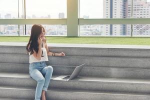 femme travaillant à l'aide d'un téléphone et d'un ordinateur à l'extérieur photo