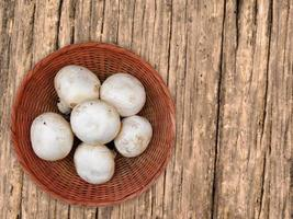 Champignons blancs sur une plaque en osier sur un fond de table en bois photo