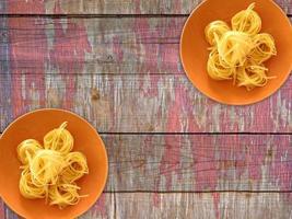 Pâtes sur une plaque orange sur un fond de table en bois photo