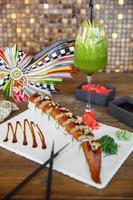 Rouleaux de sushi unagi servis sur planche de pierre blanche avec cocktail kiwi