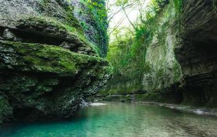 eau de rivière bleue et mousse verte sur les rochers photo