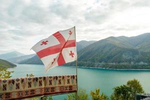 drapeau géorgien avec un fond de paysage de montagne photo