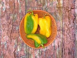 Poivrons verts et jaunes sur une plaque en osier sur un fond de table en bois photo