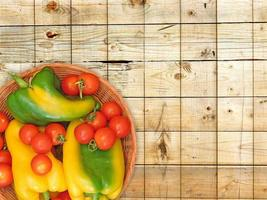 Poivrons verts et jaunes et tomates sur une plaque en osier sur un fond de table en bois photo