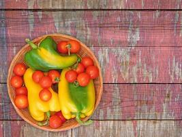 Poivrons verts et jaunes et tomates sur une plaque en osier sur un fond de table en bois