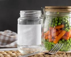 Vue avant des pois marinés et des carottes miniatures dans des bocaux en verre transparent photo