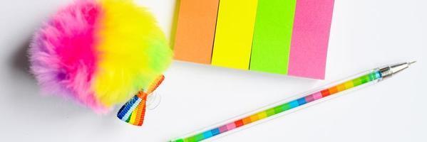 autocollants multicolores et un stylo sur fond blanc photo