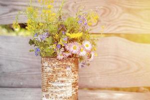 un bouquet de fleurs sauvages de myosotis, de marguerites et de pissenlits jaunes en pleine floraison dans un pot rustique photo