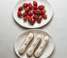 éclairs glacés blancs servis avec des fraises