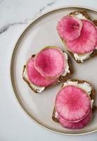 Sandwichs au radis melon d'eau et fromage à la crème sur seigle élevé sur assiette photo